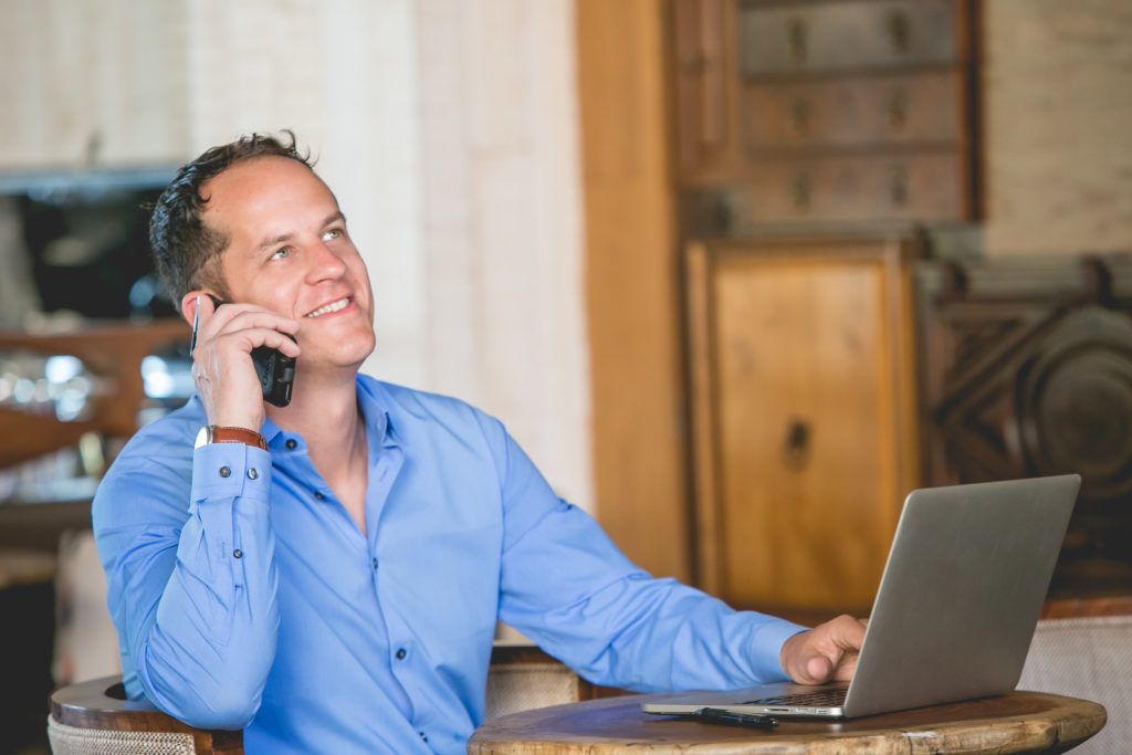 Smiling male employee taking phone call